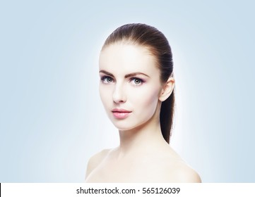 Portrait of young, beautiful and healthy woman: over cold cyan background. Healthcare, spa, makeup and face lifting concept.