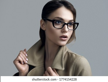 Portrait of young beautiful hipster woman in fashionable coat and eyeglasses posing on dark grey background in studio