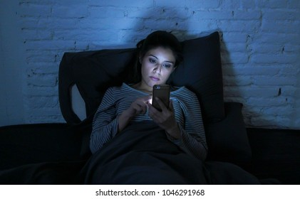 portrait of young beautiful hispanic woman using mobile phone late night sleepless lying in bed in the dark in smartphone and internet dating app addiction concept and communication lifestyle