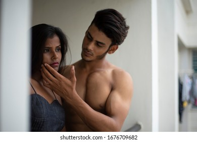 Portrait of an young and beautiful Indian brunette Bengali couple in western dress interacting themselves on a balcony in white background. Indian lifestyle.