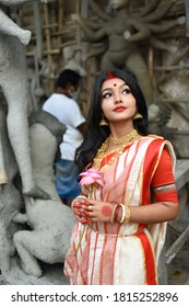 Portrait of a young and beautiful Indian woman in red and white traditional ethnic sari and gold jewellery in front of the clay idol of hindu goddess Durga. Indian culture, religion and fashion