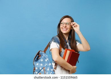 Portrait of young beautiful joyful woman student holding glasses with backpack school book looking aside on copy space isolated on blue background. Education in high school university college concept