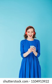 Portrait of young beautiful lady in blue dress listening music in headphones while standing with cellphone on over pink background
