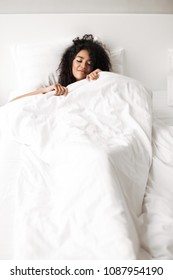 Portrait of young beautiful lady with dark curly hair lying in bed at home isolated