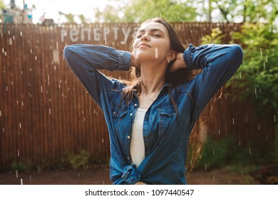 Portrait of young beautiful lady in denim shirt dreamily closing her eyes while standing under rain in park