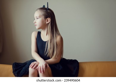 Portrait of young beautiful lonely model fashion child girl with long blond hair sad face and fancy toy ears on head in black costume
