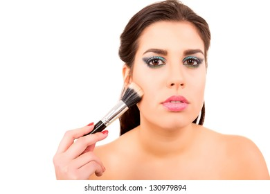 Portrait of a young and beautiful makeup artist with brushes