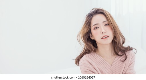 Portrait of young beautiful makeup asian woman relax pink face. Smile happy asian beauty teenage girl on winter background banner. Makeup Japanese Chinese hygge lifestyle facial treatment glow skin
