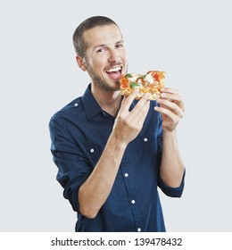 portrait of a young beautiful man eating a slice of pizza margherita