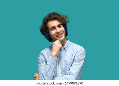 Portrait of a young beautiful man wearing white t-shirt and blue shirt in headphones over blue background