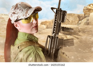 Portrait of young and beautiful military soldier woman with red hair holding an automatic rifle M16, on desert background.