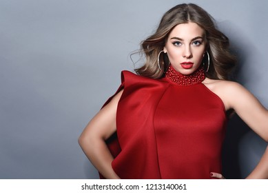 Portrait of young beautiful model with perfect make up and curly hair blown by the wind wearing red luxurious sleeveless dress with stand up collar decorated with beads and hoop earrings.  Text space