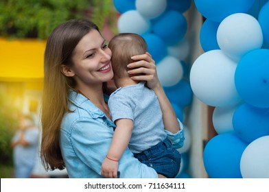 Portrait of young beautiful mom hugging and caressing her baby boy on balloons background