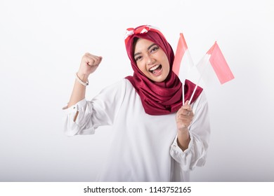 portrait of young beautiful muslim woman with indonesian flag. independence day