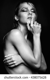 Portrait of young beautiful nude woman with wet shining  makeup and closed eyes on black background