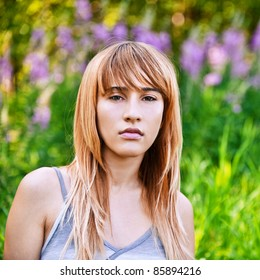 Portrait of young beautiful pensive blond woman at summer green park.