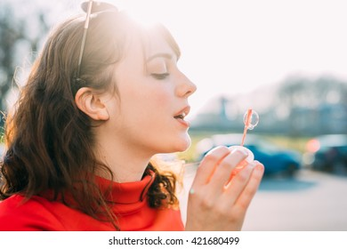 Portrait of young beautiful red dressed vintage hipster woman playing with bubble soap blowing - childhood, having fun, happiness concept