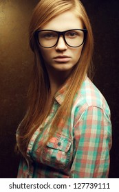 Portrait of a young beautiful red-haired wearing trendy glasses and casual shirt and posing over golden background. Close up. Studio shot.