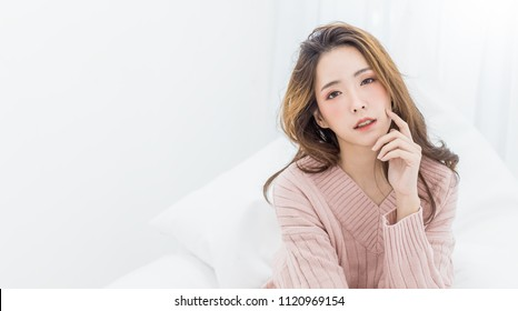 Portrait young beautiful sexy asian woman relax in bedroom. Smile happy face asian girl on white background. Beauty treatment perfect clear skin japanese korean makeup lifestyle cold winter concept