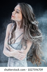 Portrait young beautiful sexy brunette with long hair woman covered with powder on black background. Portrait Of Beautiful Young Woman Covered With White Cosmetic Powder.