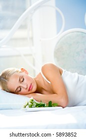 Portrait of young beautiful sleeping woman with gifts on bed at bedroom