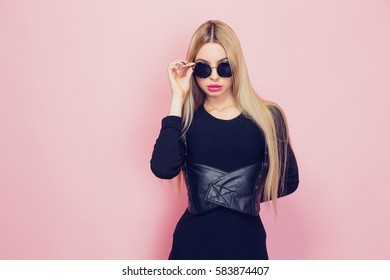 Portrait of young beautiful slim sexy young blonde woman in black sexy dress with red sensual lips on pink background in studio wearing sunglasses