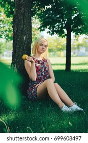 Portrait of a young beautiful smiling blonde at outdoor in the park with the apple in her hands