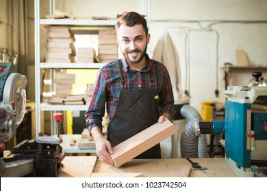 portrait of a young beautiful smiling Caucasian carpenter holding a wooden bar