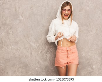 Portrait of young beautiful smiling girl in trendy summer hipster sport clothes. Sexy carefree woman posing near gray wall. Positive model having fun in sunglasses. Winking