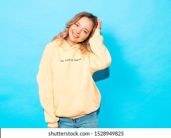 Portrait of young beautiful smiling girl in trendy summer hipster yellow hoodie.carefree woman posing near blue wall in studio. Positive model having fun
