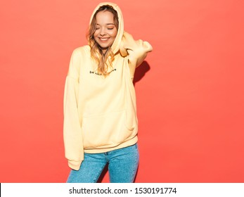 Portrait of young beautiful smiling girl in trendy summer hipster yellow hoodie.carefree woman posing near pink wall in studio. Positive model having fun