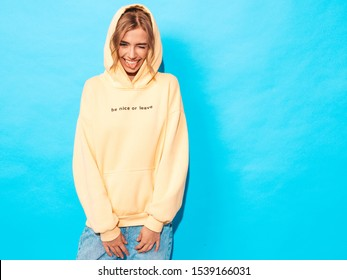 Portrait of young beautiful smiling girl in trendy summer hipster yellow hoodie.Sexy carefree woman posing near blue wall. Positive model having fun.Winks and shows tongue - Shutterstock ID 1539166031