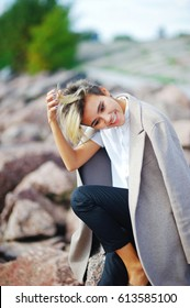 Portrait of young beautiful smiling girl sitting on rock, on coast to coat draped over the shoulders, on blurred background, close up.