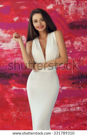 4d3900fcd2ac7 Portrait of young beautiful smiling girl wearing white evening dress with  decollete