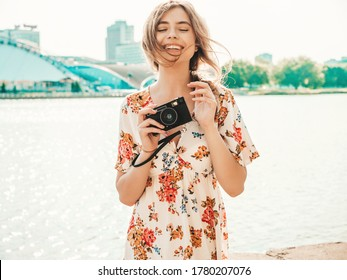 Portrait of young beautiful smiling hipster girl in trendy summer sundress.Sexy carefree woman posing on the sea background at sunset. Positive model holding retro camera - Shutterstock ID 1780207076