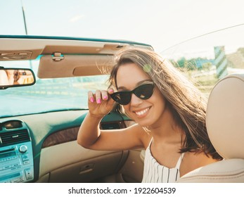 Portrait of young beautiful and smiling hipster female in convertible car. Sexy carefree woman driving cabriolet. Positive model riding and having fun in sunglasses at sunset