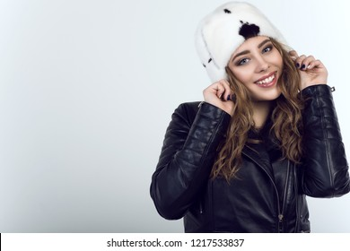 Portrait of young beautiful smiling model wearing trendy black leather unzipped moto jacket and white mink fur hat with black spots. Isolated on white background. Text space. Studio shot