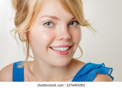 Portrait of a young beautiful smiling woman. The girl is looking at the camera with a smile