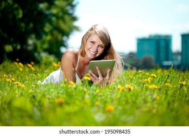 Portrait of young beautiful smiling woman with tablet pc, outdoors. Beautiful young girl lying on the grass in the field. Smiling trendy stylish woman on nature