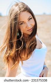 Portrait of the young beautiful smiling woman outdoors enjoying summer sun
