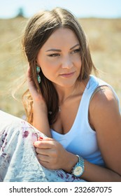 Portrait of the young beautiful smiling woman outdoors enjoying summer sun. wind in hair