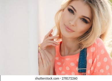 Portrait of the young beautiful smiling woman outdoors enjoying summer sun. Photo with instagram style filters. Young woman outdoors portrait. Soft sunny colors. Beautiful blonde woman outdoor