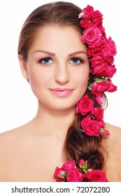 Portrait of young beautiful smiling woman with roses in hair, on white background
