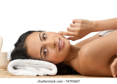 Portrait of young beautiful spa woman lying on bamboo mat and smiling. Isolated on white background.