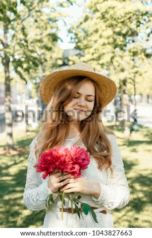 portrait of young beautiful stylish girl in park holding peony bouquet in  front of face beb057e19