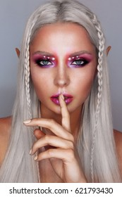 Portrait of young beautiful tanned platinum blonde woman with bright make up. Elf girl.