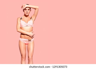 Portrait of young beautiful tanned woman in pink  bikini posing on pantone 16-1546 living coral color background.