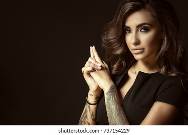 Portrait of young beautiful tattooed woman with luxuriant shining wavy hair and perfect make up holding her hands in shooting gesture in the shape of the gun. Studio shot. Copy space