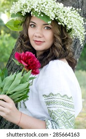 Portrait of a young beautiful in traditional Ukrainian embroidered shirt and a wreath of lilies of the valley on the head