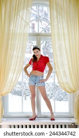 Portrait  of young beautiful vintage brunette woman on the windows looking the camera with hands on his hips. Sensual model girl in vintage clothing inside a luxury hotels room in winter time.